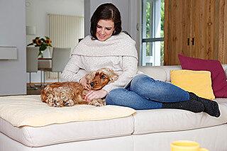frau kuschelt mit hund auf dem sofa