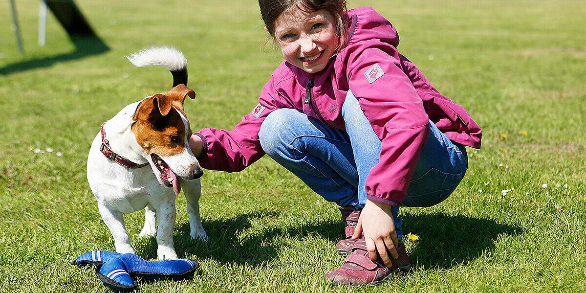Mädchen spielt mit Hund