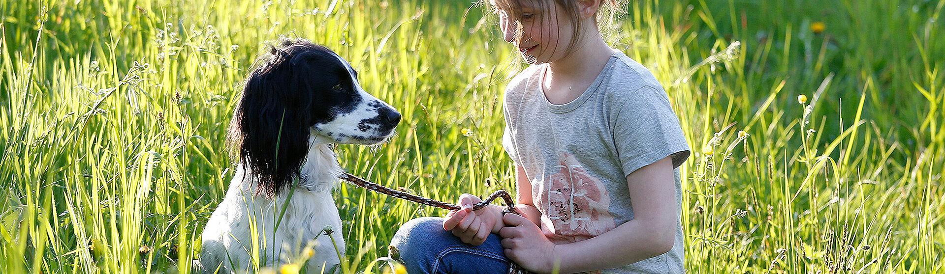 Mädchen liegt mit einem Hund auf dem Sofa